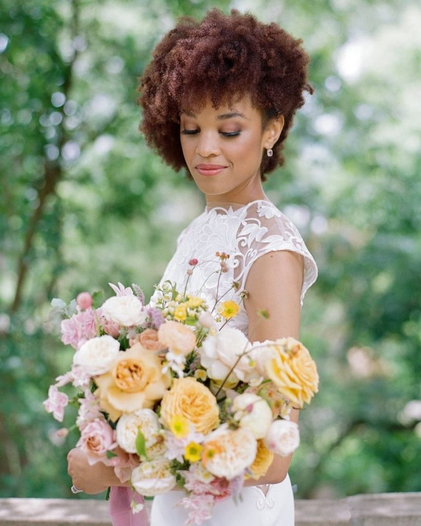makeupatx styled this bride's natural curls in an elegant, pinned side-sweep and romantic bridal makeup that has us seriously SWOONING!